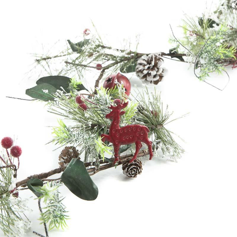 Snowy artificial pine and jingle bell garland christmas
